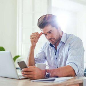 homme avec un telephone portable devant un ordinateur